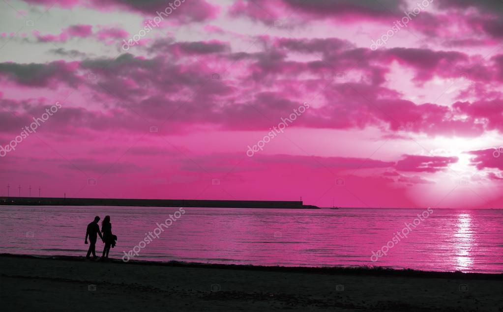 silhouette of a young couple walking by the sea