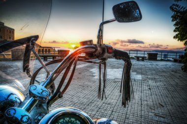 classic motorcycle by the sea at sunset