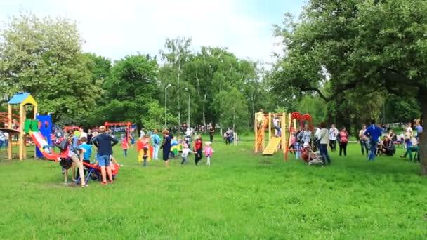 Kinder spielen auf dem Spielplatz mit den Eltern