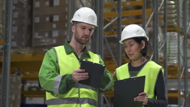male and woman colleagues discuss working process. warehouse coworkers looking
