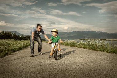 Happy father and son on bicycle