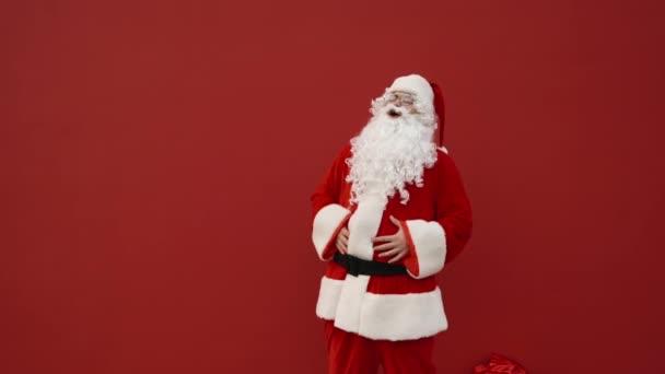 Pozitivní muž v kostýmu Santy se emocionálně směje na červeném pozadí a drží se za břicho. Santa usmívá na Vánoce na červeném pozadí zdi.