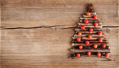 Christmas card with natural decorations on wooden background