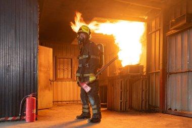 İtfaiyeci ya da üniformalı bir itfaiyeci sıcak ateşe karşı yangın hortumu ve konteynırdaki tehlikeli dumana karşı acil bir kaza kurtarma operasyonu kullanıyor. - İnsanlar. Kahraman