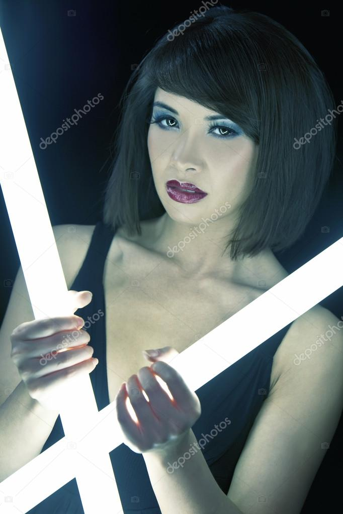 A stunningly beautiful young Asian Chinese woman holding glowing  fluorescent tubes in a night club — Photo by ...