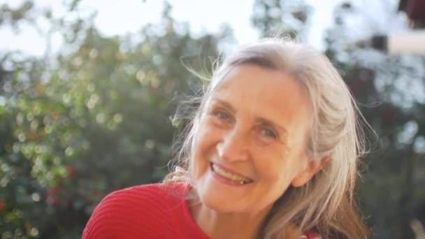 Közelkép boldog mosolygós idősebb nő szürke hajjal nézi a kamerát, miközben időt tölt a szabadban a napsütéses napon