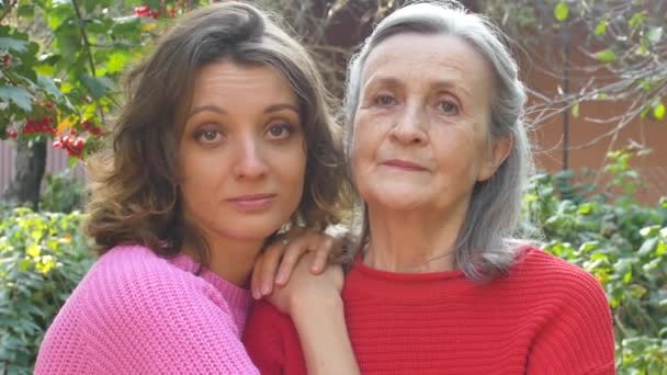 Starší matka s šedivými vlasy se svou dospělou dcerou dívá na kameru v zahradě a objímají se během slunečného dne venku
