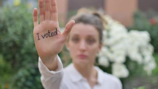 Szabadtéri női portré fiatal felnőtt nő fehér ing mutatja a kezét szlogennel szavaztam virágok háttér, választások nap koncepció