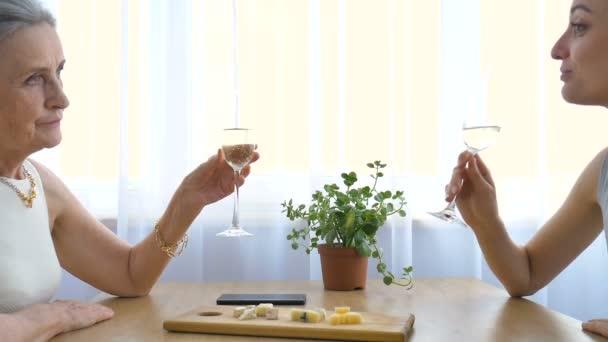 Frauenporträt von erwachsener Tochter und älterer Mutter, die zu Hause am Tisch sitzt und Champagner trinkt, glücklicher Ruhestand, Muttertagskonzepte, Alkoholsucht