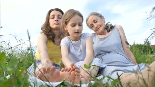 Cute child girl with her young mother and senior grandmother are having picnic during summer outdoor in nature, mothers day, happy retirement, multi generation family