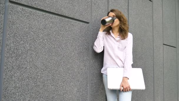 Female portrait of young woman with silver laptop and cup of coffee waiting for a meeting near dark grey wall in the morning, remote job, coffeebreak, smart student concept