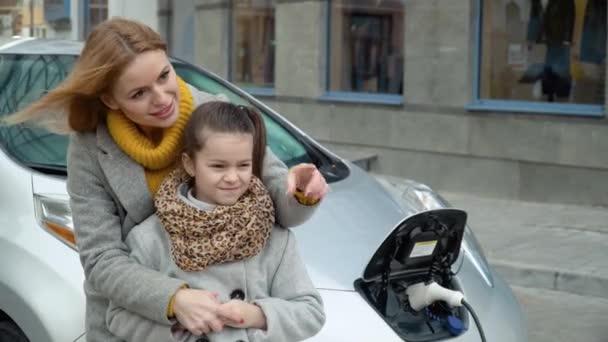 U jejího elektrického auta stojí žena s dcerou. Nabíjení elektromobilu na čerpací stanici