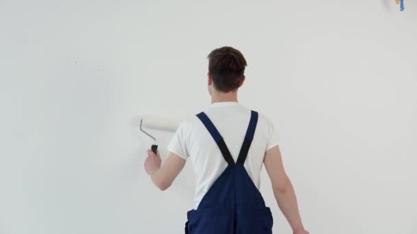 Maler mit Walze in der Hand bemalt eine weiße Wand. Blick von hinten