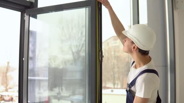Instalátor oken měří rozměry rámu okna pomocí měřicí pásky