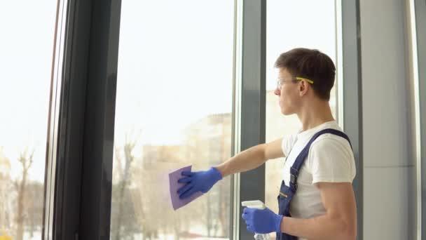 Junger Soldat in Schutzuniform und Brille wäscht Fenster