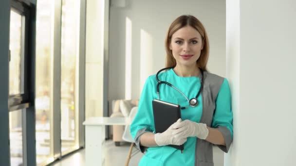 Doktorka v lékařském kabátě a stetoskopu s dokumenty v rukou, dívající se do kamery. Usmívající se lékařka nebo sestra v nemocniční ordinaci