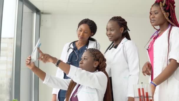 Junge afrikanische Ärzte untersuchen ein Röntgenbild, während sie an einem Tisch stehen