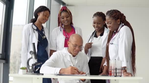 Eine Gruppe von vier afrikanisch-amerikanischen Studenten diskutiert ein Röntgenbild mit dem Arzt, der einige Notizen macht