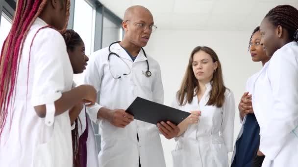 Egy csapat orvos, köztük nemzetközi férfi és nő, üzleti beszélgetést folytat, miközben egy klinikán áll.