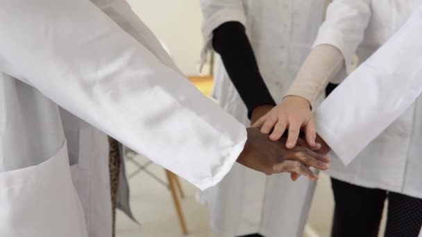 A team of doctors, including women and men of different nationalities, make a gesture of unity. Close-up shooting of hands