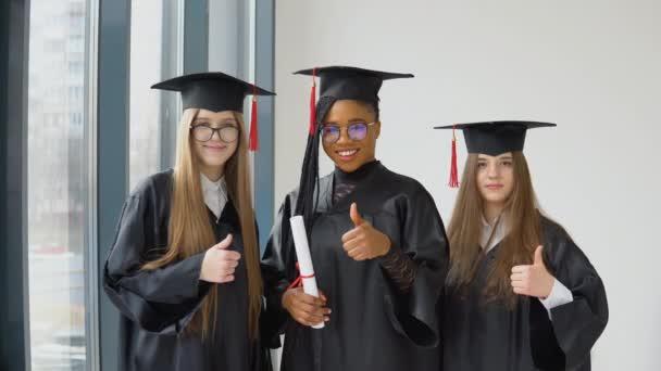 Tři studentky různých ras s diplomem v ruce. Absolventi v černém rouchu a s hranatými klobouky se na kameru dívají s úsměvem. Grand for higher education in Europe and the United States