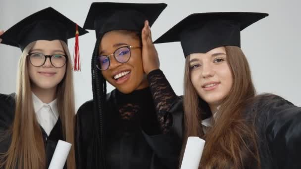 Tři mladé šťastné absolventky různých národností stojí bok po boku s diplomy v rukou. Zavřít pohled na bílém pozadí