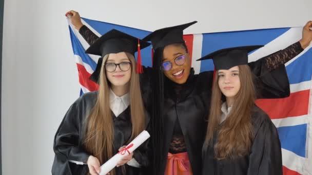 Tři mladé šťastné absolventky různých národností stojí bok po boku s diplomy v rukou a za nimi britská vlajka. Zavřít pohled na bílém pozadí