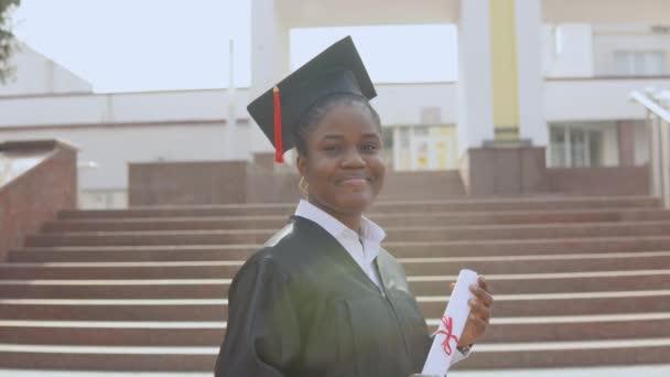 Mladá africká americká absolventka, stojící před kamerou s diplomem a knihami v rukou. Student je oblečen v černém rouchu a čtvercový mistr klobouk a stojí venku.