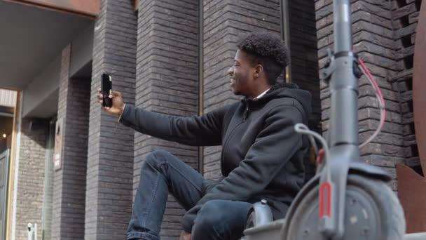 Ein junger Afroamerikaner in schwarzem Pullover, Jeans und Turnschuhen sitzt auf dem Bürgersteig in der Nähe eines Gebäudes mit dunkler Backsteinfassade. Der Typ macht ein Selfie mit einem Elektroroller