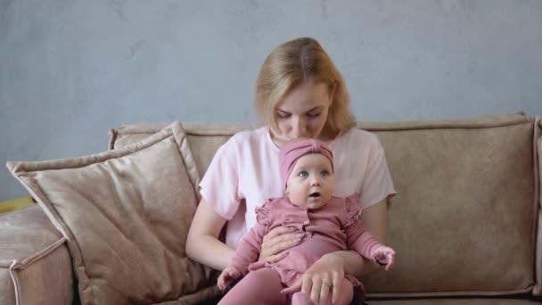 Baby dívka roztomilé hraní zbraně matka pohovka domů