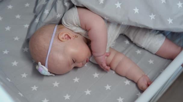 Das kleine Mädchen schläft in einer Wiege mit grauem Bettzeug und macht eine Saugbewegung mit dem Mund. Das Baby träumt vom Stillen