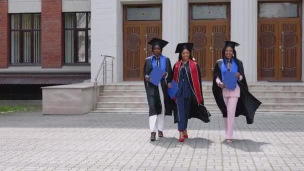 Šťastní absolventi univerzity nebo vysoké školy afroamerické národnosti s modrými diplomy v rukou jdou před kameru od vstupu na univerzitu