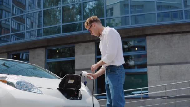 Stylový moderní mladý kudrnatý muž v džínách a bílé košili na dvoře obytného komplexu spojuje elektrické auto nabíjet