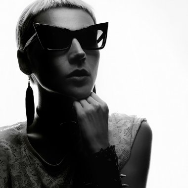 Sensual blond in trendy sunglasses and jewelry. Black and white