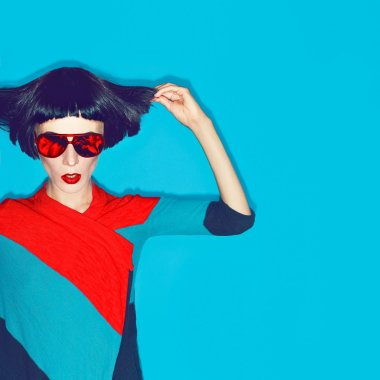 brunette model with fashion haircut and sunglasses on a blue bac
