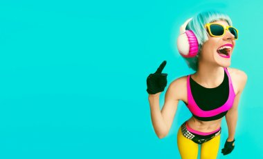 Glamorous fashion dj girl in bright clothes on a blue background