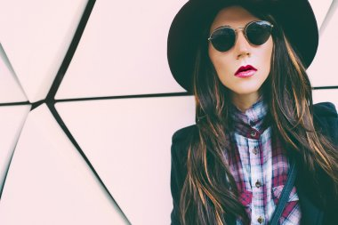 Girl in vintage hat and sunglasses on a city street. fashion sty