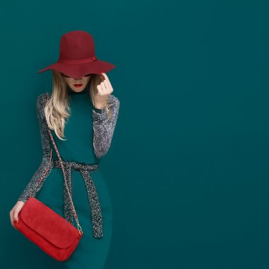 Lovely blond model in fashionable red hat and a red clutch on gr