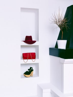 Women's fashion accessories in white interior. Hat, clutch and s
