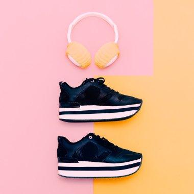 Trendy white headphones and sneakers on vanilla background. Urba
