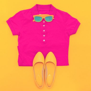 Set of sunglasses shirt and shoes on a yellow background. Bright