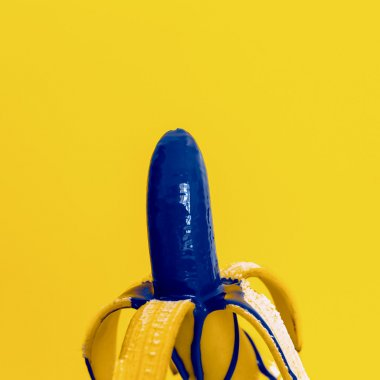 Glamorous banana with blue paint on yellow background. Bright su