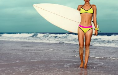 Stylish girl on the beach with a surf board