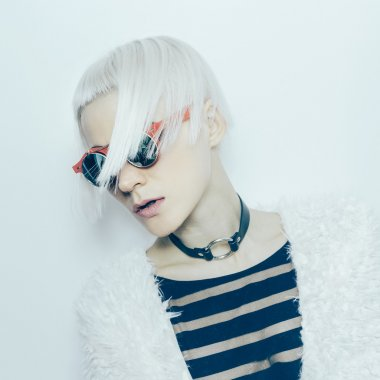 Sensual blonde girl in stylish sunglasses and accessories neck