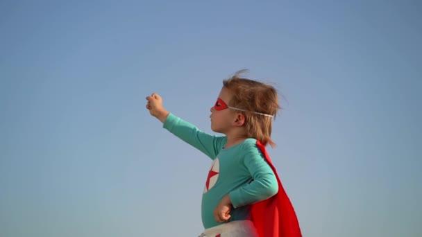 Szuperhős gyermek kék ég háttér. Szuperhős kölyök játszik a szabadban. A gyermekek álma és képzelőereje