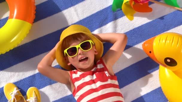 Boldog gyerek, aki jól érzi magát a nyári szünetben. Gyerek élvezi a nap a strandon törölköző