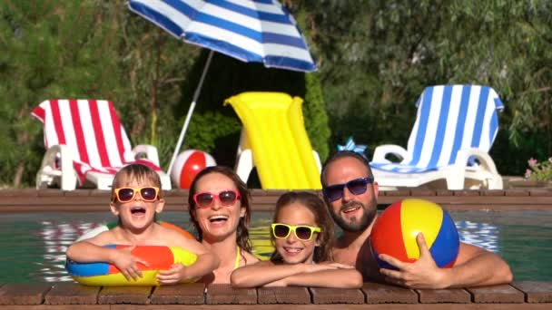 Happy family having fun in swimming pool. Mother, father, daughter and son on summer vacation