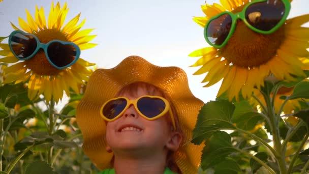 Šťastné dítě se baví na jarním poli slunečnic. Vtipné dítě si užívá letní prázdniny