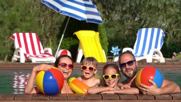 Happy family having fun in swimming pool. Mother, father, daughter and son on summer vacation. Slow motion