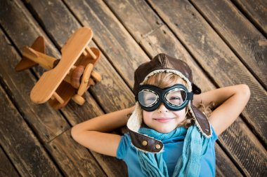 Child pilot with vintage plane toy on grunge wooden background stock vector